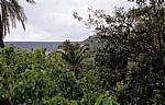 Blick durch einen Garten auf die Stadt - Bosa