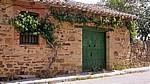 Jakobsweg (Camino Francés): Traditionelles Haus mit Holztür und rankendem Wein - El Ganso