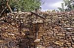 Jakobsweg (Camino Francés): Steinmauer mit Holzkreuz - El Ganso