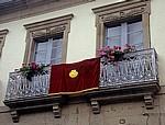 Jakobsweg (Camino Francés): Wandteppich mit Jakobsmuschel zwischen zwei Balkonen - Sarria