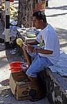 Ananasverkäufer beim Schälen einer Ananas - Pereybere